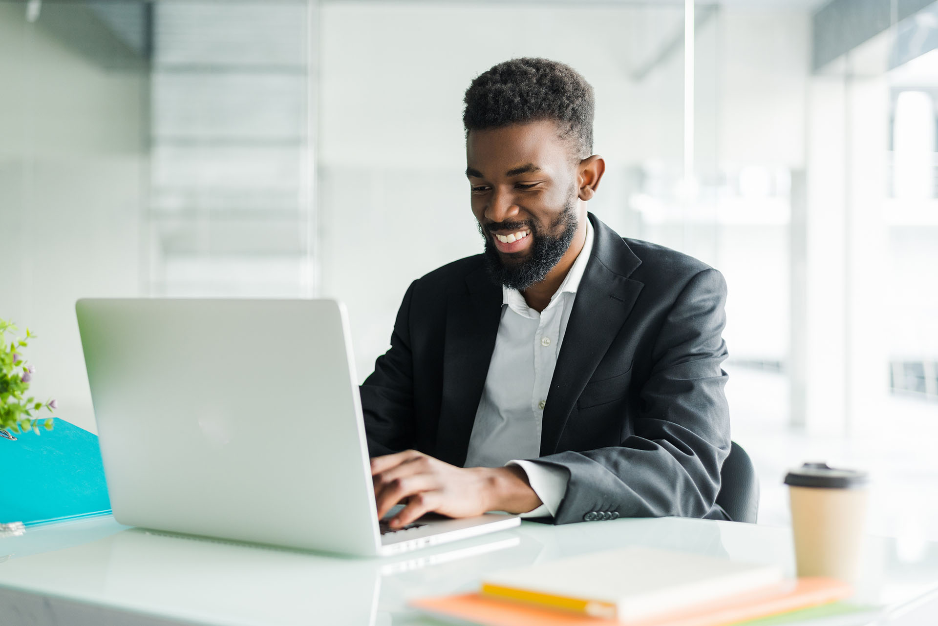 Thoughtful African American businessman wearing glasses using laptop, pondering project, business strategy, puzzled employee executive looking at laptop screen, reading email, making decision